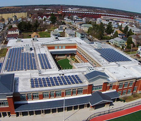An image of a large building with many solar panels on top of it