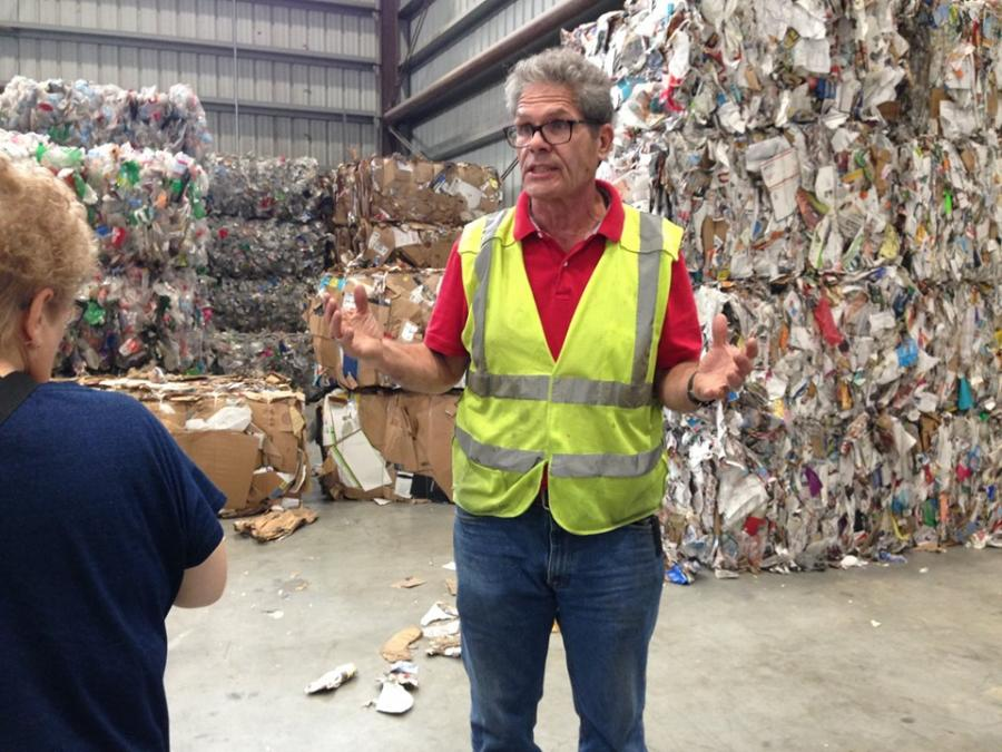 A man in a safety vest is explains recycling in front of bales of recyclable material