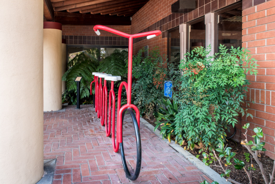 Photo of a red metal bike rack shaped to look like a 4 seat bike with handlebars. The rack is on a brick patio outside a brick building with green landscaping.