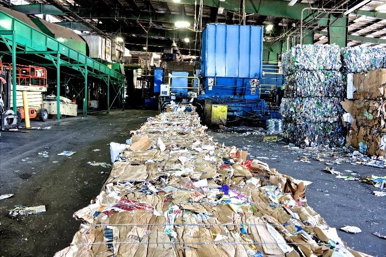 A photo of a waste processing facility with large cubes of compacted waste