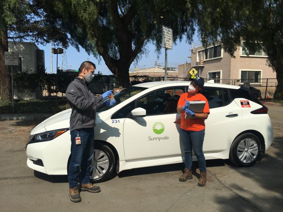 Photo of two people standing in front of a white electric vehicle with the Sunnyvale logo on the driver side door.