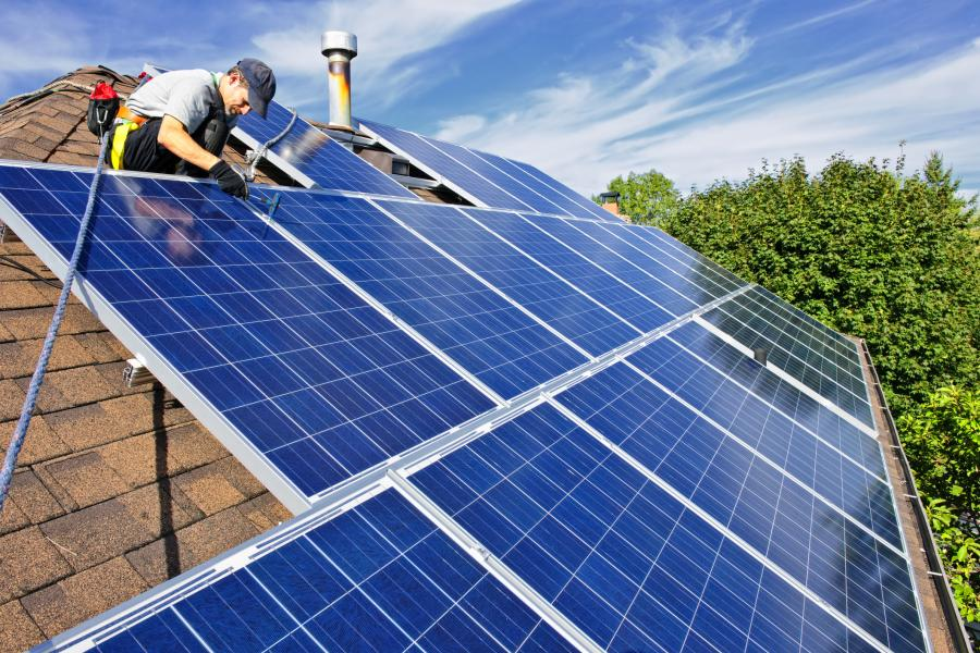 Person working on solar panels on a rooftop