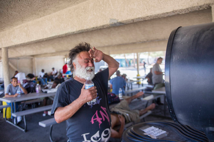 Man with a beard standing in front of a fan to cool down