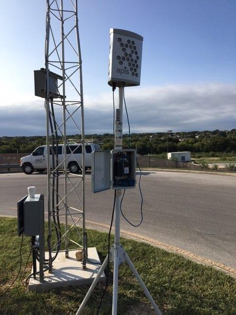 A picture of an air quality monitoring device, which is a large rectangular object on a tall tripod.